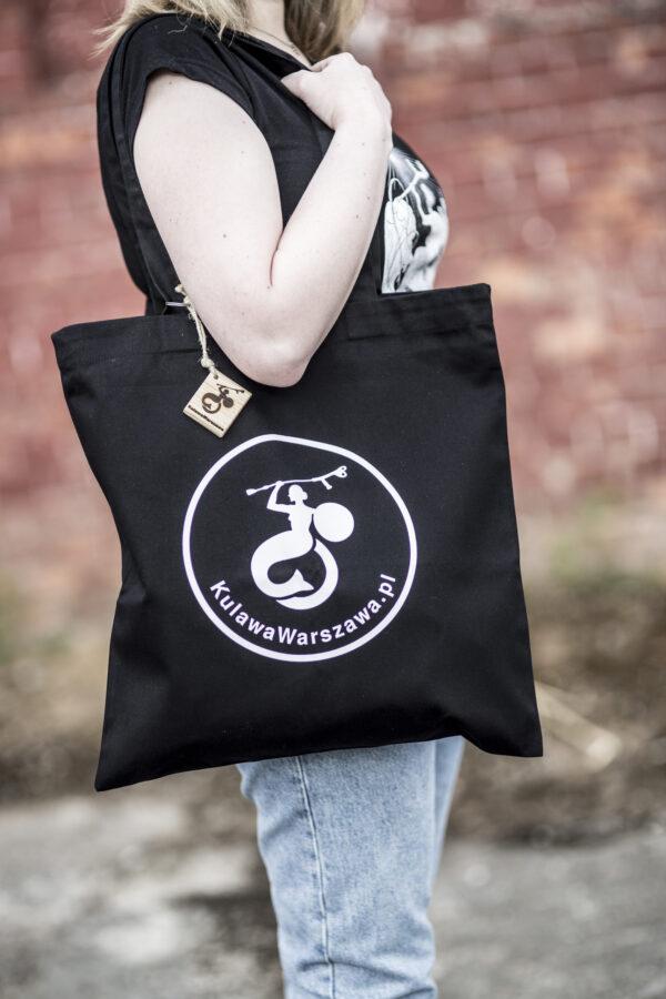 kobieta z torbą materiałową z logo Fundacji Kulawa Warszawa, breloczkiem z logo fundacji