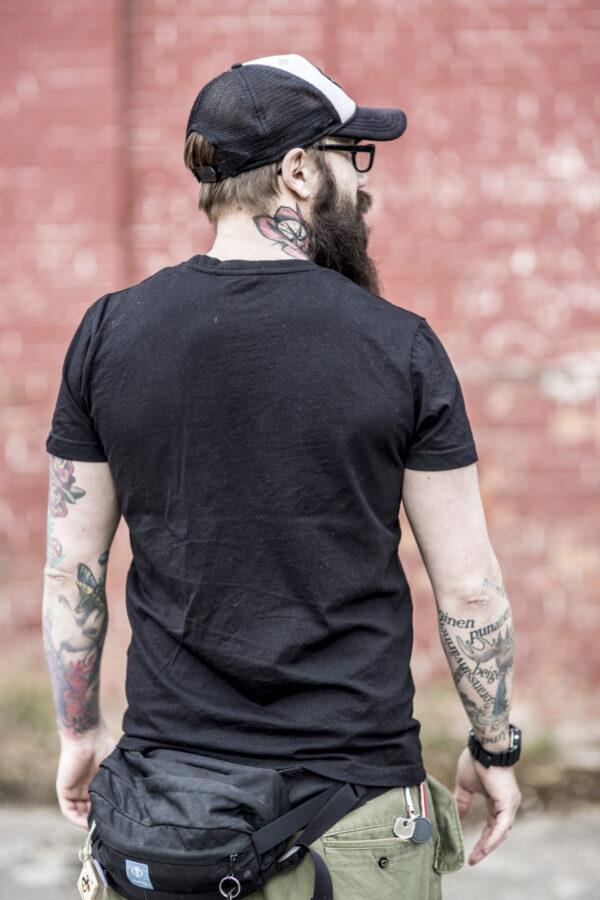 Wytatuowany mężczyzna z brodą stoi tyłem