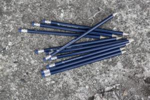 kilka granatowych ołówków gumką z napisem Fundacja Kulawa Warszawa i logo syrenki warszawskiej na wózku i z kulą w ręce