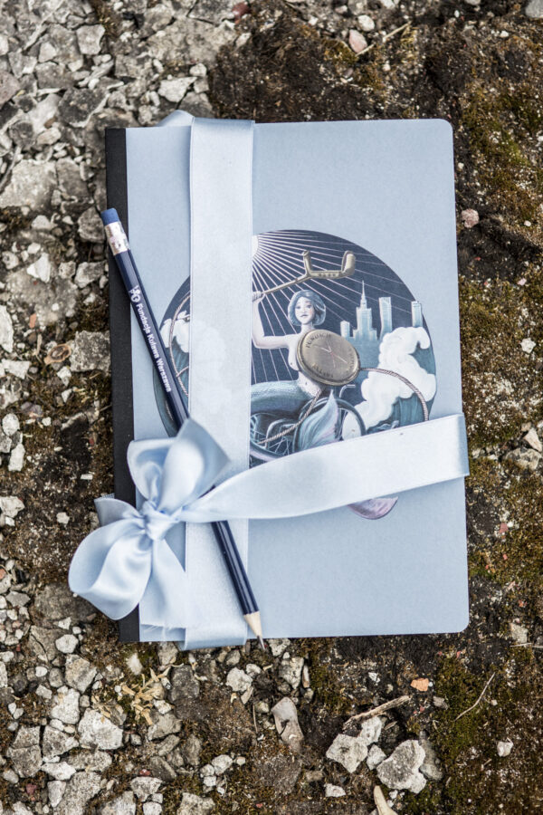 zestaw niebieski notes z syrenką na wózku i ołówek z napisem Fundacja Kulawa Warszawa. Wszystko przewiązane błękitna wstążką