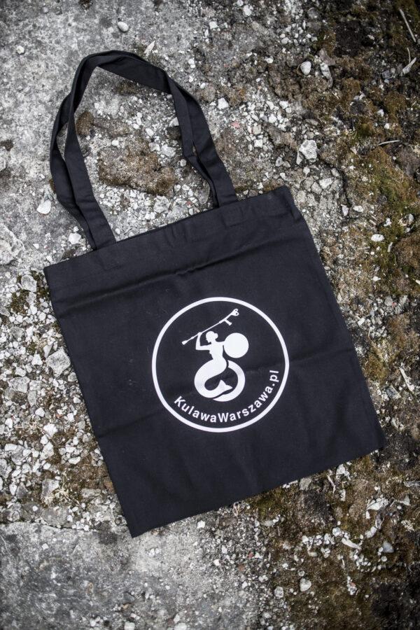 Czarna torba z jedną z wersji logo Fundacji Kulawa Warszawa. W okręgu piktogram syrenki warszawskiej na wózku z kulą w ręce, a pod nim zaokrąglony napis KulawaWarszawa.pl