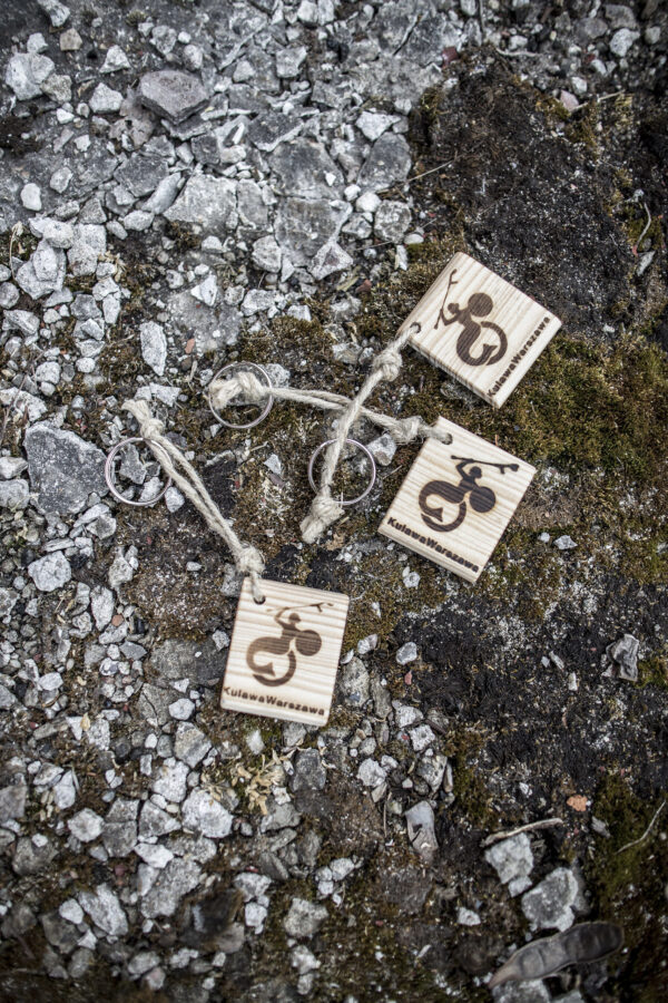 Na drewnianej kwadratowej deseczce wypalone logo Fundacji Kulawa Warszawa przyczepiona na sznurku do kółeczka do kluczy