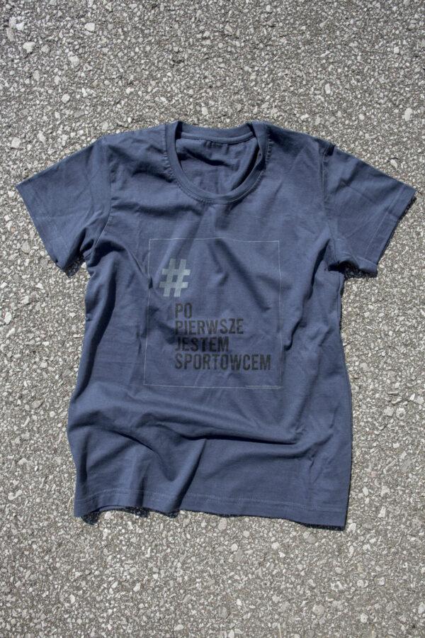 grafitowo niebieska koszulka z logo kampanii - prostokątna jasnoszara ramka z napisze # (w kolorze szarym) Po Pierwsze Jestem Sportowcem (w kolorze czarnym) małymi szarymi literami napis Fundacja Kulawa Warszawa
