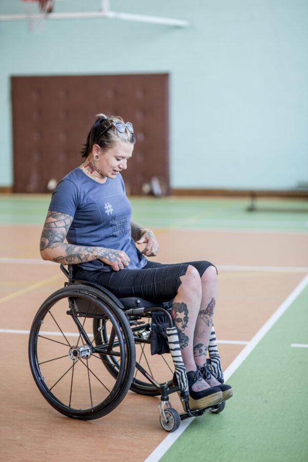 Kobieta na wózku w grafitowo niebieskiej koszulce z logo kampanii - prostokątna jasnoszara ramka z napisze # (w kolorze szarym) Po Pierwsze Jestem Sportowcem (w kolorze czarnym) małymi szarymi literami napis Fundacja Kulawa Warszawa