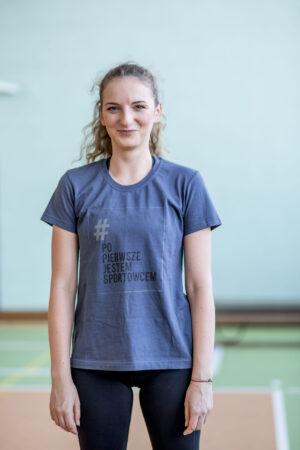 Stojąca kobieta w grafitowo niebieskiej koszulce z logo kampanii - prostokątna jasnoszara ramka z napisze # (w kolorze szarym) Po Pierwsze Jestem Sportowcem (w kolorze czarnym) małymi szarymi literami napis Fundacja Kulawa Warszawa