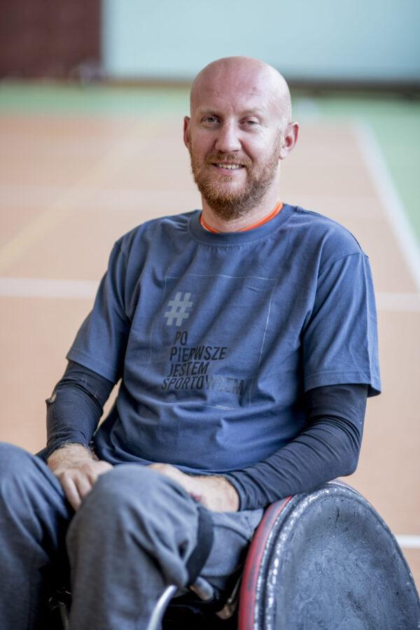 Mężczyzna na wózku rugowym w grafitowo niebieskiej koszulce z logo kampanii - prostokątna jasnoszara ramka z napisze # (w kolorze szarym) Po Pierwsze Jestem Sportowcem (w kolorze czarnym) małymi szarymi literami napis Fundacja Kulawa Warszawa