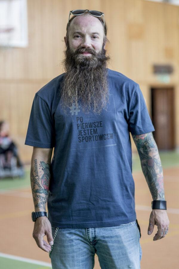 Stojący mężczyzna z długą brodą w grafitowo niebieskiej koszulce z logo kampanii - prostokątna jasnoszara ramka z napisze # (w kolorze szarym) Po Pierwsze Jestem Sportowcem (w kolorze czarnym) małymi szarymi literami napis Fundacja Kulawa Warszawa