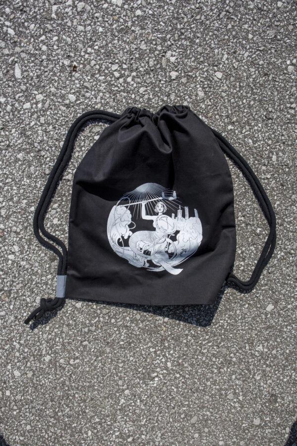 Czarny plecak w stylu worek, na grubych sznurkach z małymi kawałkami szarek odblasku u dołu. Nadruk na plecaku przedstawia syrenkę na wózku z kulą ręce