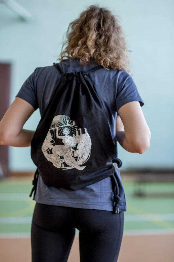 Młoda dziewczyna stoi tyłem na plecach ma czarny plecak w stylu worek, na grubych sznurkach z małymi kawałkami szarek odblasku u dołu. Nadruk na plecaku przedstawia syrenkę na wózku z kulą ręce