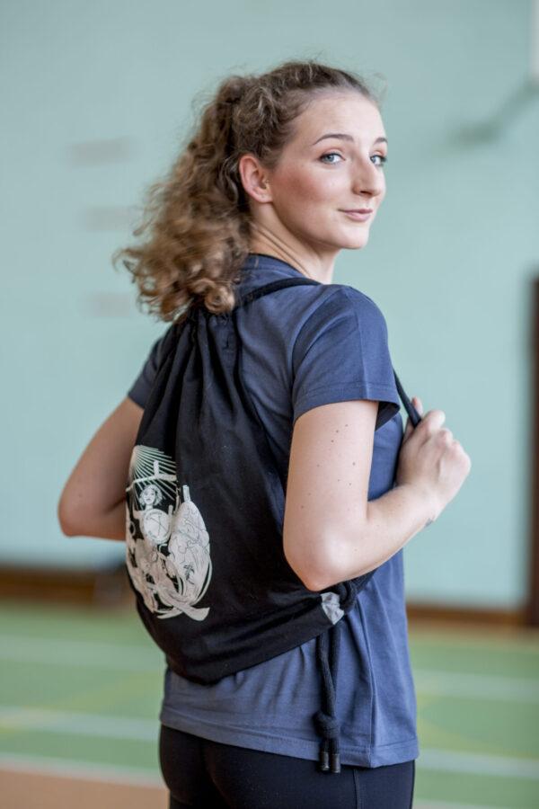 Młoda dziewczyna stoi prawie całkowicie tyłem, odwracał głowy w stronę obiektywu na plecach ma czarny plecak w stylu worek, na grubych sznurkach z małymi kawałkami szarek odblasku u dołu. Nadruk na plecaku przedstawia syrenkę na wózku z kulą ręce